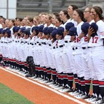 17 women baseball players lined up with their blues over their white uniforms