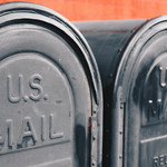 "Two black mailboxes that say ""U.S. Mail"" side by side on the sidewalk"