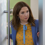 Ellie Kemper holds the door to her office open with a serious expression on her face