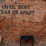 "A brick wall with the words ""until debt tear us apart"" in black block letters"