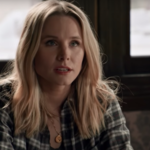 Veronica Mars, a white woman, sits at her desk at work. She wears a flannel and has blond hair parted down the middle.