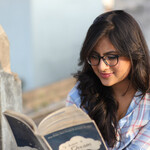 an Indian woman with shoulder-length brown hair and glasses sits outside and reads a book
