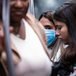 a woman wearing a protective mask rides a subway in New York City