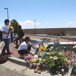 People placing flowers beside a makeshift memorial outside the Cielo Vista Mall Wal-Mart where a mass shooting left at least 20 people dead on August 4, 2019 in El Paso, Texas.