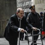 Harvey Weinstein, an older white man, hunches over a walker as he walks into court