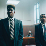 Jharrel Jerome (left) and Asante Blackk (right) stand next to each other in a courtroom, both wearing suits