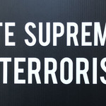 "A black sign with the words ""white supremacy is terrorism"" in white"
