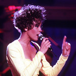 Whitney Houston in 1991, wearing a pale yellow jumpsuit and singing into a microphone