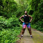 a Black woman wearing workout clothes, a black shirt and shorts, stands in a forest with her hands on her hips
