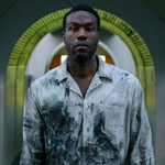 Yahya Abdul-Mateen II plays Anthony, a dark-skinned, tall Black man, who is wearing a paint-splattered jean jacket in Candyman