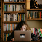 a white teenager with curly, brown hair sits at a desk with a library behind her as she does her schoolwork on a gray Macbook Air