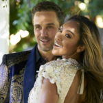 Zac C, a white man with brown hair who is wearing a suit, poses beside Tayshia Adams, a Black woman with long, flowing hair and is wearing a white wedding gown, on The Bachelorette