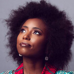 Zakiya Dalila Harris, a dark-skinned Black woman with a black afro, crosses her arms that are covered in a pink and teal patterned blazer