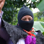 a zapatista woman with a black mask over her head raises her hand