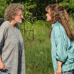 Two women have a heated discussion while standing in a grassy field.