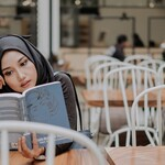 A woman in a black hijab reads in an open space.