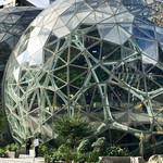 Amazon's spherical headquarters feature three large glass domes with tall buildings visible in the background
