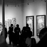 Black and white photo of people attending an art exhibit