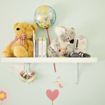 a photo of a nursery shelf with a stuffed koala bear, a stuffed teddy bear, and other gifts for a baby