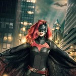 A white woman with long red hair stands in front of a city at night. A light in the shape of a bat is projected into the sky. She is wearing a black mask and skintight catsuit with a red bat across the chest.