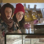 two white women, one wearing a brown scarf and one wearing a burgundy hat, stand in a deli