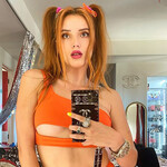 Bella Thorne, who is thin and white, wears an orange crop top with cut outs and has bright red hair in pigtails.