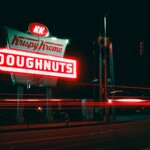 A Krispy Kreme sign glows on a street.