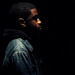 A side view of a Black teenage boy wearing a hoodie and jean jacket against a black background