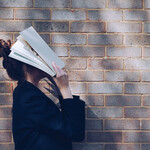 A woman with a bun holds a book over her face.