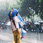 an Asian child smiling and standing in the rain with a jacket over her head