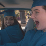 two white teenagers in graduation regalia smile and laugh in a car