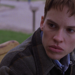 A close up of Brandon, played by Hilary Swank, a white teen boy with brown hair looks away from the camera