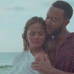 Chrissy Teigen leans against husband John Legend on a beach.
