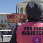 "A person in a hoodie standing in front of the Supreme Court with their back turned, wearing a bright pink vest that reads, ""Pro-Choice Clinic Escort"""