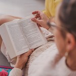 A person with light brown hair and glasses reads a book while wearing a white sweater.