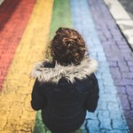 a child with brown hair and a black jacket sitting in front of a rainbow-colored sidewalk