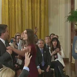 A White House intern attempts to take the microphone from reporter Jim Acosta at the Wednesday press conference