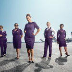 Five flight attendants model Delta's purple uniforms on an airport tarmac with a blue sky and planes in the background
