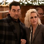 A white guy with glasses and dark hair and a short white woman with messy bleach blond hair stand next to each other in fancy holiday outfits, looking shocked and upset.