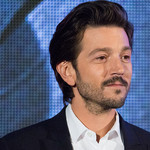 Diego Luna smiles casually, there is a blue screen behind him