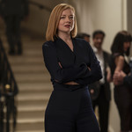 Sarah Shook, a white actress with short, red hair, wears a black suit, on Succession