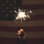 Hand holding a sparkler in front of an American flag