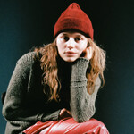 girl in red, a white singer wearing a gray sweater, red hat, and red leather pants, sits on a chair in front of a teal background