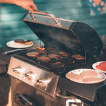 A person holding a beer and lifting the lid of a grill, hamburgers and hot dogs are cooking
