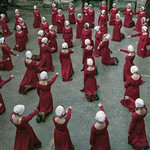 Dozens of women wearing red robes and white bonnets kneeling in a circle
