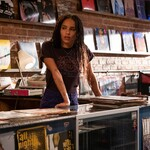 Zoë Kravitz as Rob, a light-skinned Black girl with long braids who stands behind the counter of a record store, in High Fidelity