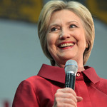 Hillary Clinton wearing a red top, smiling at an unseen audience and holding a microphone