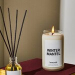 "A candle that reads ""winter mantel"" sits on a red book next to a reed diffuser."
