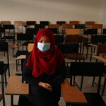 A student wearing a red headscarf and a medical face mask is staring directly at the camera. They are alone in a classroom with empty desks behind them.