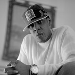 A young Jay-Z in black and white wears a t-shirt and a hat.